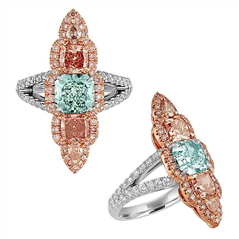 1.57 Carat Cushion GIA Fancy Blue Green in Color and SI1 in Clarity, 0.61 Carat Cushion GIA Certified Fancy Intense Orangey Pink in Color and VS2 in Clarity plus 0.58 Carat Cushion Fancy Deep Orangey Pink in Color and VVS2 in Clarity are set in 18K
