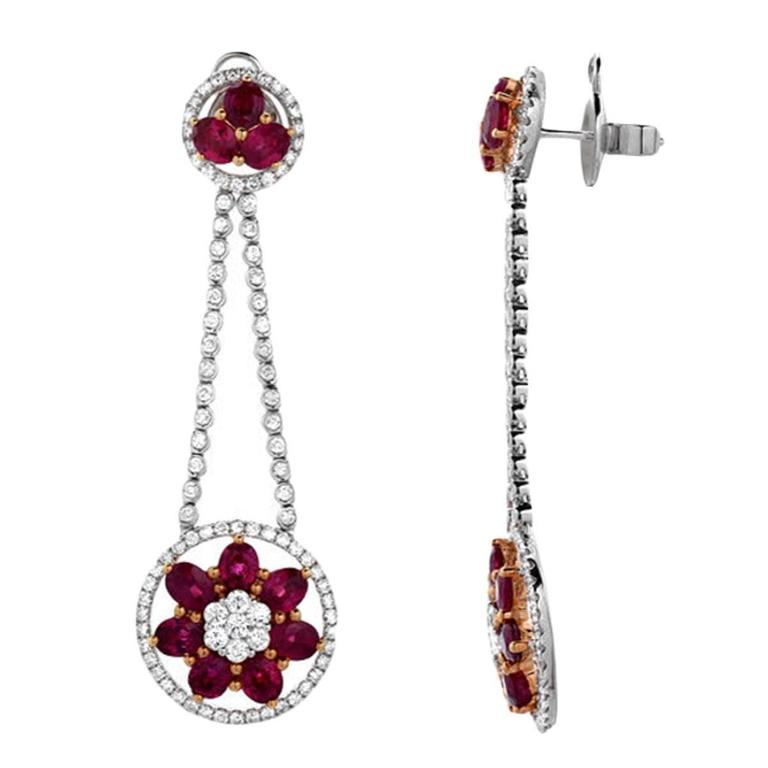 A feminine pair of earrings featuring 8.82 carats of oval shaped vivid red rubies and 2.96 carats of VS quality round cut diamonds. The pendulum style earrings have a soft movement to them, set in 18K gold.  Earring Length: 2.45 inches Earring