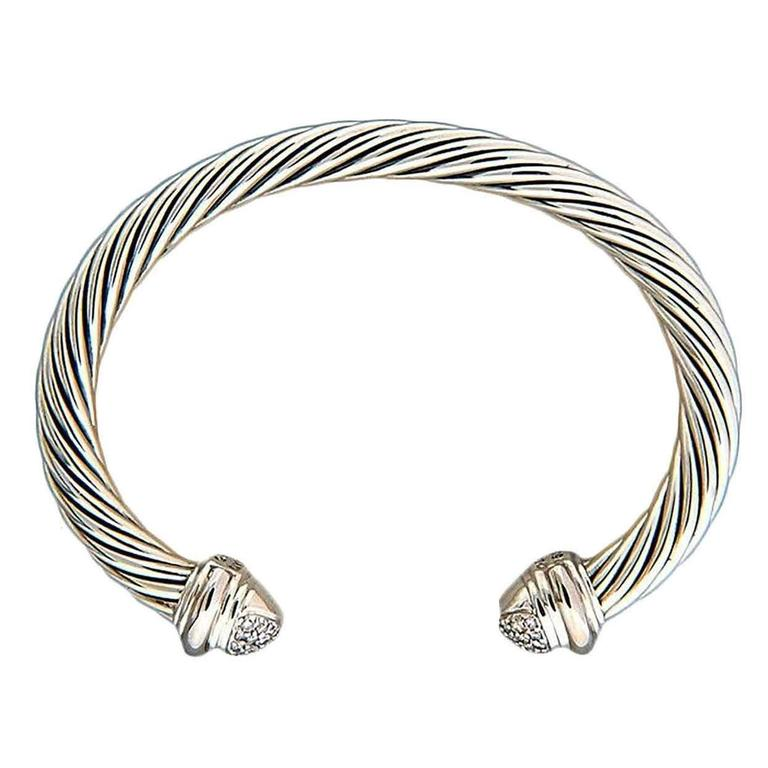 David Yurman 7mm silver cable bracelet with 18k white gold diamond end caps.  40 full cut diamonds, approx. total weight .55cts, H, SI1 18k white gold caps Silver 43.26 grams 7mm silver cable bracelet Stamped: D Yurman 750 925 Oval shape 2.55 x 1.7