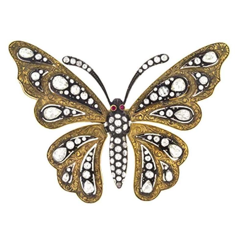 The body and antennae of the butterfly are bead-set with rose-cut and single-cut diamonds with 2 bezel-set ruby eyes, the wings are intricately engraved gold bead-set with round and pear-shaped rose-cut and single-cut diamonds and are movable (set