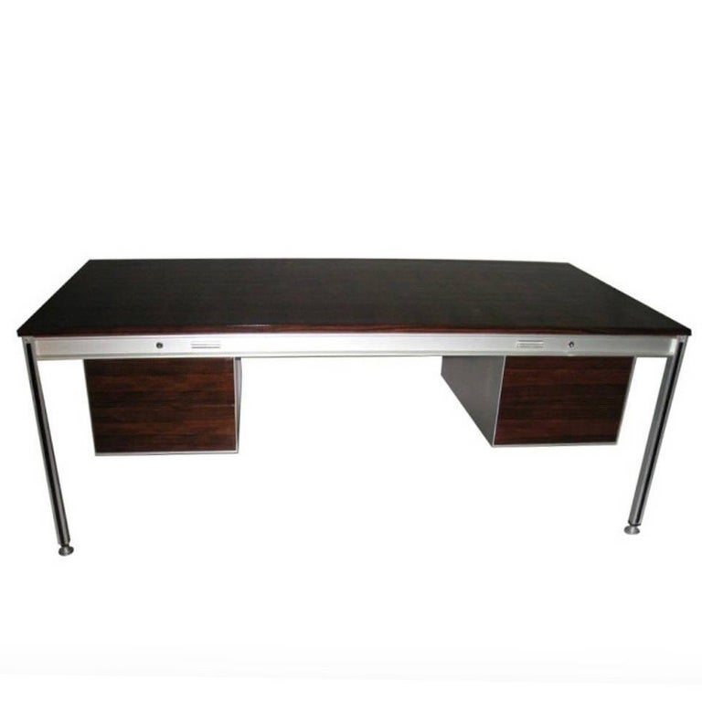 Firmly structured executive desk by Claude Gaillard and Henri Lesetre for T.F.M. The desk has a lacquered rosewood top, a brushed aluminium frame,  four legs each with a vertical band of black laminate that conceals screws and a total of three