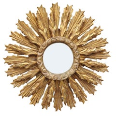 Continental Carved Giltwood Sunburst Mirror with Layered Rays and Cloudy Motifs