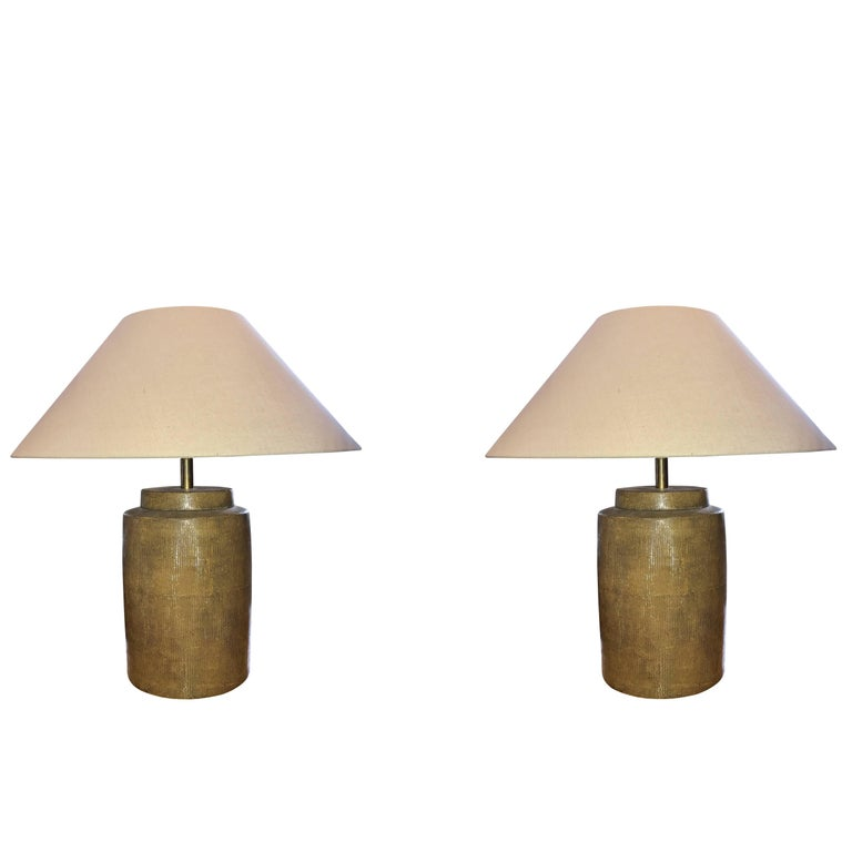 Contemporary Chinese pair of porcelain lamps with a textured gold basket weave pattern. Custom taupe linen shades. Shade diameter is 20