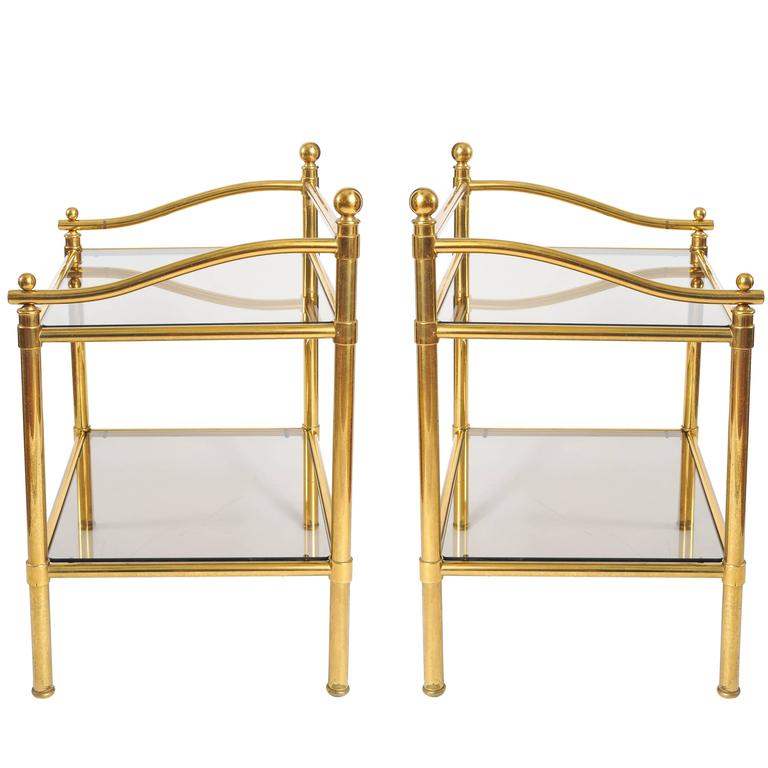 Elegant brass side tables with decorative curved sides and raised back frame, finished with brass finials. Two shelves of smokey glass.