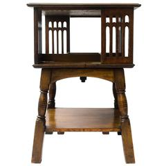 Liberty & Co An Arts & Crafts Oak Revolving Bookcase Table on Square Turned Legs