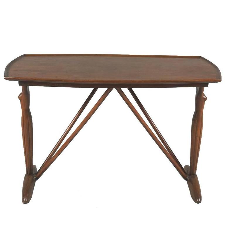 Danish 1930s-1940s walnut side table. The dished top raised on two figurative female end supports.