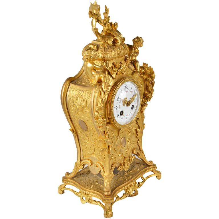 A good quality 19th century Louis XVI style gilded ormolu mantel clock, having scrolling C scroll and foliate decoration with putti on either side of the enamel dialled clock face, chiming on the hour and half hour and eight day duration.