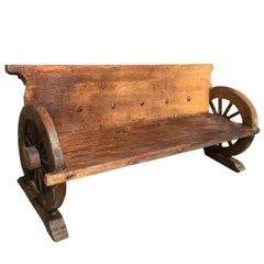 Rustic Bench with Antique Wheels and Iron Studs