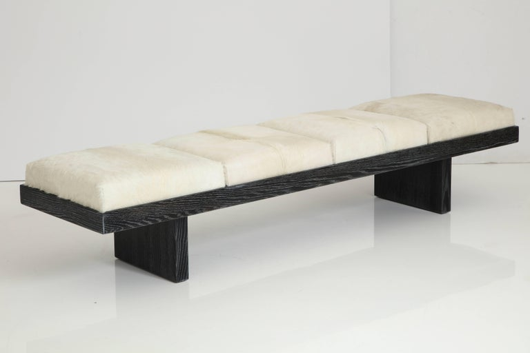 Modern plinth base solid Oak bench with a custom cerused black or white finish with four white calf skin hide seats. Labeled.