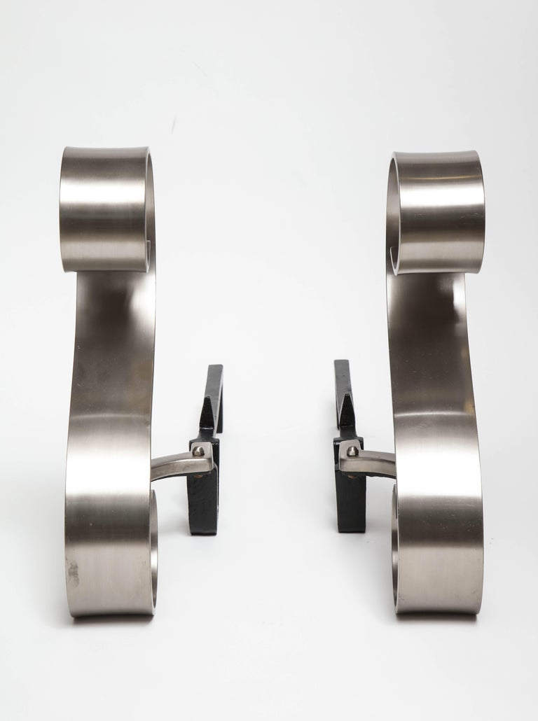 Pair of graceful Art Deco scroll motif andirons in a brushed nickel finish with black iron backs.