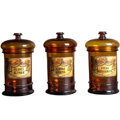 Three Balloon Lid Glass Apothecary Jars with Original Illustrative Labels