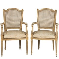 Pair of Early 20th Century French Painted and Parcel-Gilt Elbow Chairs