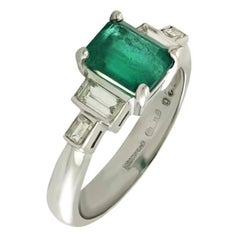 Emerald and Four White Baguette cut Diamond Ring set in 18kt White Gold