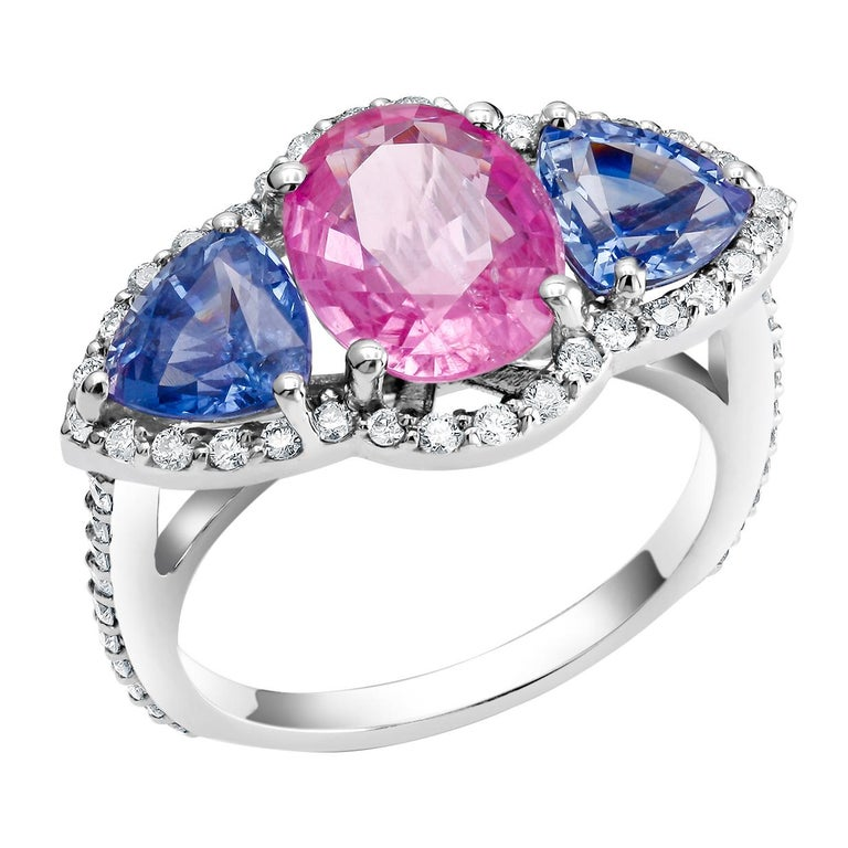 One of a Kind 18k white gold cocktail ring 2.98 carats Ceylon pink sapphire  Matched pair of trillion Ceylon Sapphire weighing 2.32  Surrounded by pave set diamonds weighing 0.75 carats   New Ring Blue, pink and yellow Ceylon Sapphires are a