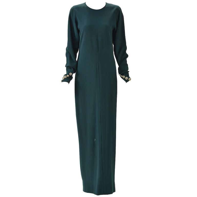 This gorgeous and glamorous Galanos long green dress is the elegance you need in your life. Scoop neck with long bat-wing sleeves are buttoned at cuffs with five silver rhinestone buttons. Open back tying at neck. Gathered at waist with back zipper.