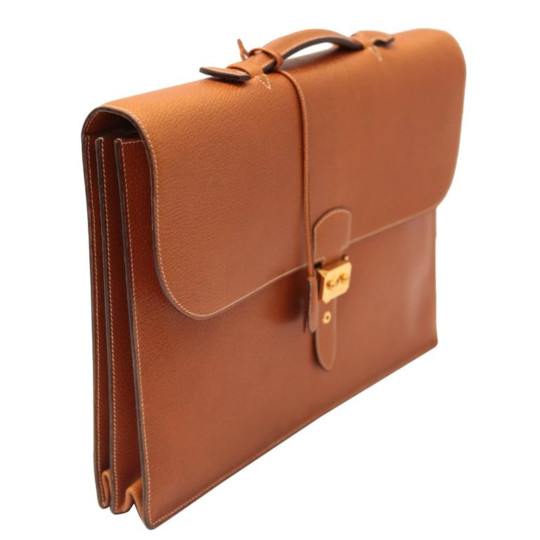 Classic leather briefcase with white stitching, gold hardware and a sliding lock clasp with key. Leather interior separated into three compartments.  A classic for any business person.