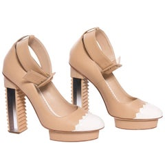 Pair of tan and white heels by Aperlai Paris