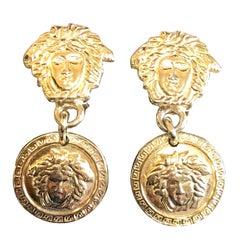 Vintage Gianni Versace gold tone medusa head, face motif dangle earrings.