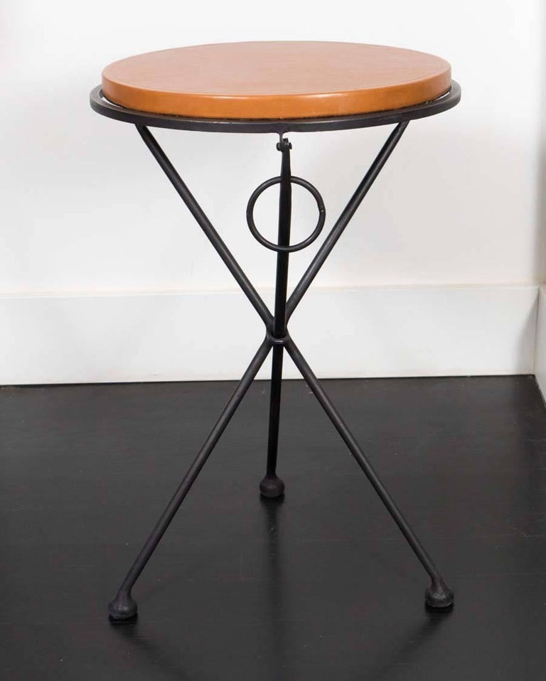 Pair of occasional tables from France. Hand forged iron base with leather covered oak tops. Once lifted by the rings, these tables fold flat.