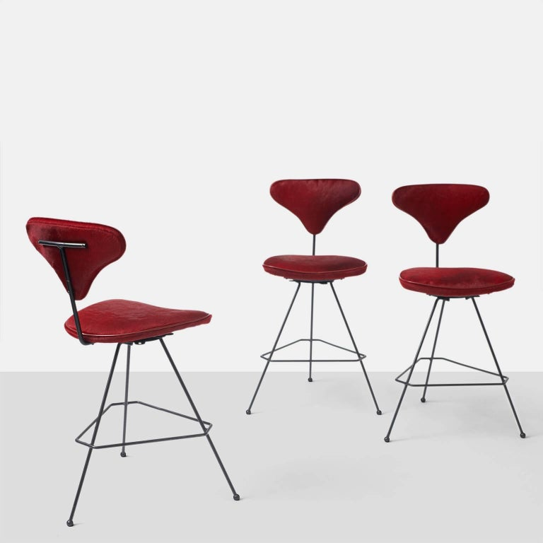 A group of three bar stools with a swivel base and black iron frame. The seat and back have been upholstered in a red hair on hide with red leather trim. The stools were made for Elton in 1950.