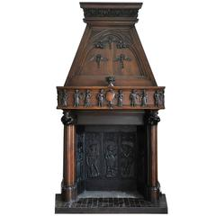 Neo-Gothic style carved walnut fireplace with hood, 19th c.