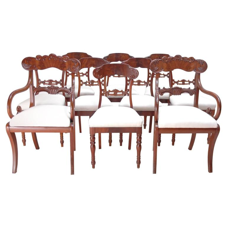 An assembled group of ten Karl Johan dining chairs comprising of a set of eight chairs without arms and a pair of arm chairs in mahogany with carved back splat and crest rail with foliate design of acanthus leaves. Side chairs feature turned front