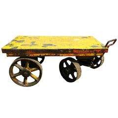 One industrial cart with handle and four iron wheels.