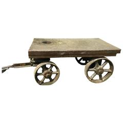 An industrial cart with handle and four iron wheels.