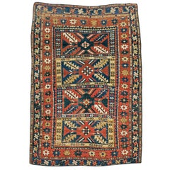 Distressed Caucasian Rug With A Tribal Design In Rust, Dark Blue, And Cream