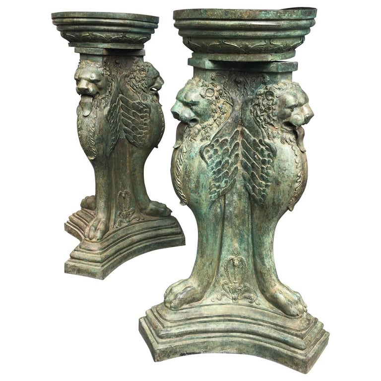 Large pair of urns in the shape of triple-winged griffins and clawed feet.