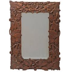 Beveled Mirror with Ornately Carved Frame, circa 1910s