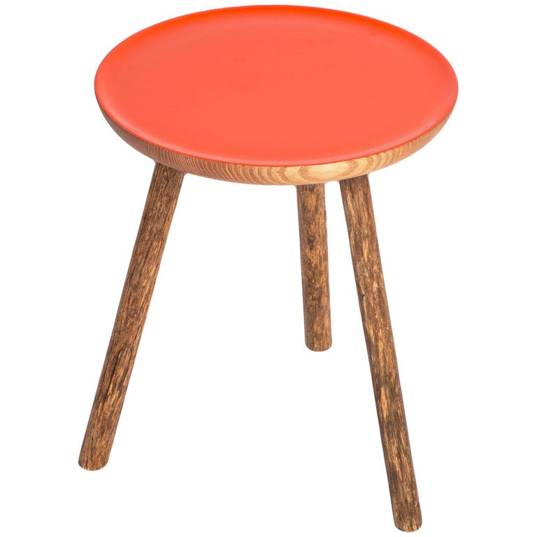 This staked wood side table with orange glossy top is a new edition from Erik Gustafson.   In Stock  Gustafson's inspiration stems from a love of the history of art, architecture and design. Gustafson pieces are inherently tactile, they invite