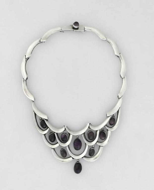Being offered is a sterling silver necklace by Antonio Pineda of Taxco, Mexico. Necklace of wavy links with 10 tear drop shaped amethysts bib. Dimensions 17 inches long, the big 2 1/2 inches at deepest.     Marked as illustrated. In excellent