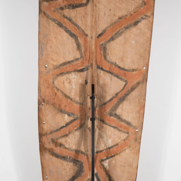 This striking shield was realized in Papua New Guinea towards the end of the 19th century. The rectangular form in unfinished nubuck hued hardwood has been inscribed with white curvilinear and geometric patterns. A small carved wood figurine adorns