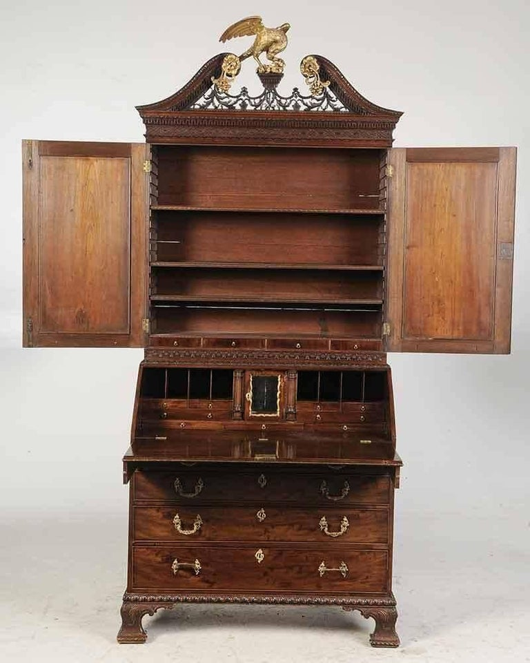 Period Chippendale George III Secretary Bookcase with Desk Interior  British, circa 1765, highly figured veneers, blind fretwork, leaf, and gadrooned carving, gilt finial rosettes and mirrored door surrounds, lower case with fitted desk interior,