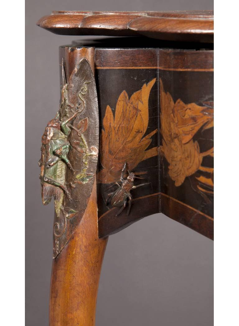 Charles-Guillaume Diehl  A rare and fine cold-painted and enameled copper mounted fruitwood inlaid table Paris, circa 1878  The table, opening to reveal a cushioned interior in red silk, raised on three intertwined curved legs with the front