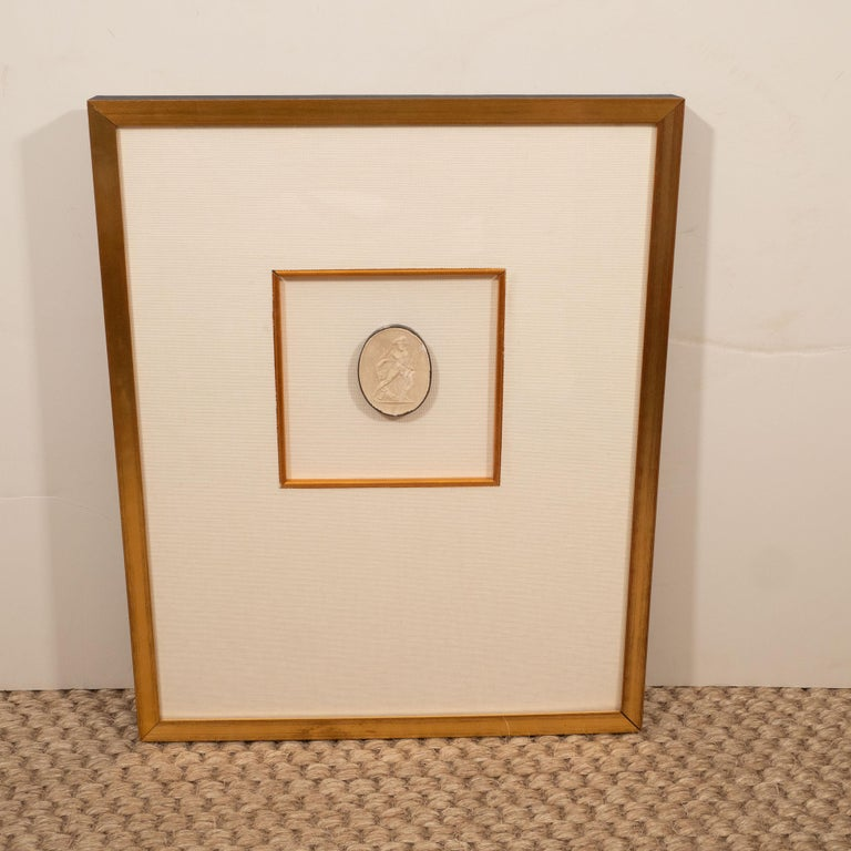 A plaster intaglio matted in linen and framed in gold frames with a lovely inner gold fillet. Neutral in color, this piece adds a quiet elegance to a room.