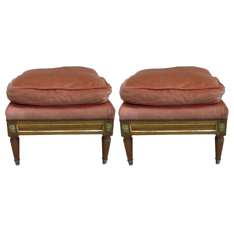 A pair of elegant Mid-Century Louis XVI style foot stools / ottomans / poofs in the modern neoclassical tradition with tapered legs ending in solid bronze sabots and brass decoration. Made by hand.