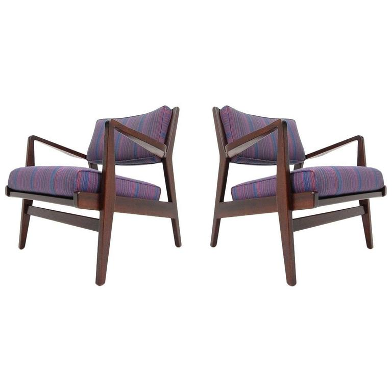 Pair of Jens Risom lounge chairs in walnut, circa 1965. Chairs have been completely refinished in a dark walnut and reupholstered, including new foam. Measures: Width 27