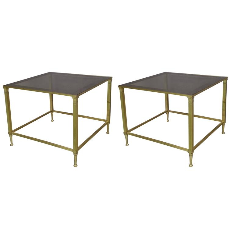 A chic pair of French brass end tables in the modern neoclassical style with delicate fluted pilaster legs and tapered sabots. Tops of smoked glass framed with dark borders.   Both pieces can be arranged to form a cocktail or coffee table (H 16 x W