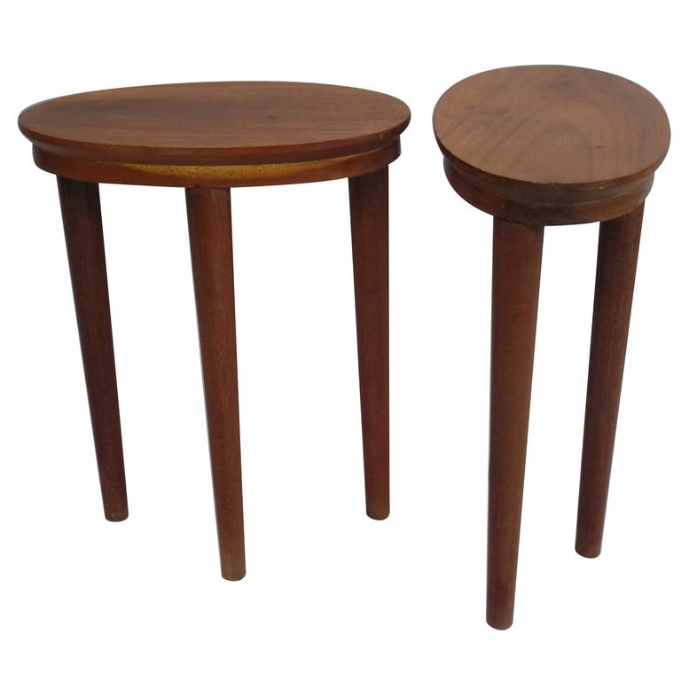 An elegant and sober pair of French 1930s Modern Neoclassical three-legged tables from French Indochina. The structure is composed of solid rosewood with an oval top gently cantilevered over an oval apron which rests on three striking tapered