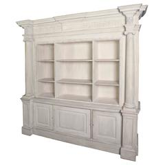 A cream painted wooden neoclassical bookcase in two sections