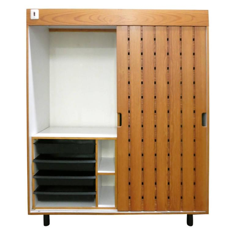 Wardrobe with a single sliding slatted wood door. The interior is white laminate with a separate pull-out cabinet with drawers in molded plastic. Each drawer is stamped