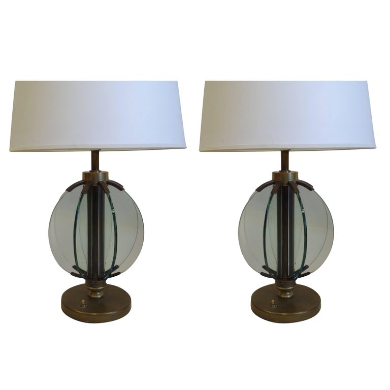 An elegant pair of Italian Mid-Century table lamps by Fontana Arte reflecting a modern neoclassical taste (Novecento) composed of a solid brass frame with inset pieces of glass arranged in the form of an astrolabe.   Fontana Arte worked with such