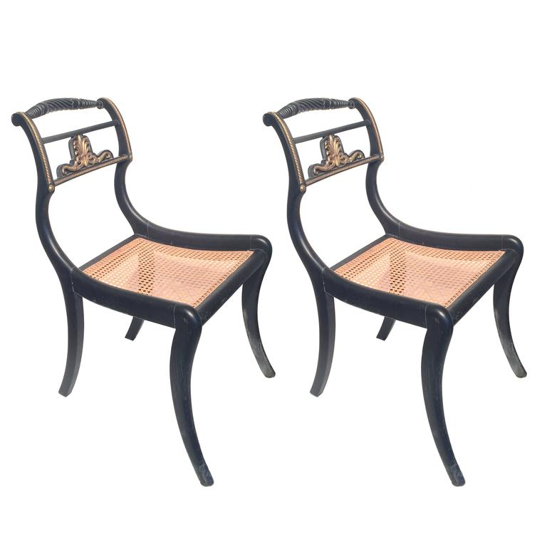 A pair of English Regency period occasional chairs, 1810. Ebonized wood, bronze ormolu and caned seats.
