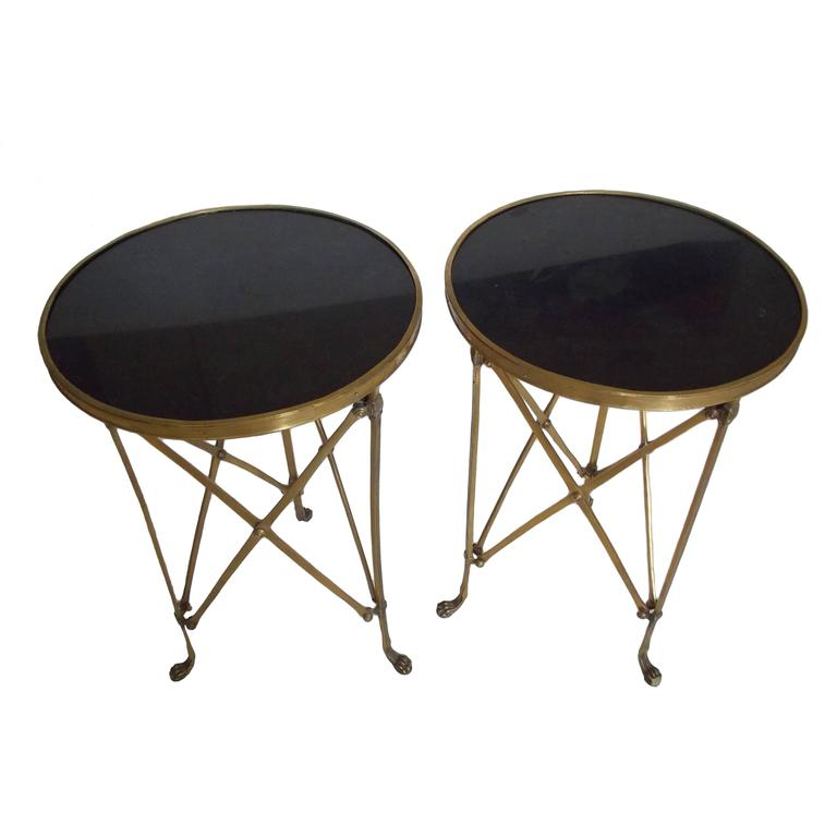 A stunning Mid-Century pair of French gueridon tables with black granite tops. The brass bases have vertical cross stretchers joined by a medallion in the center and rest upon cat paw feet.