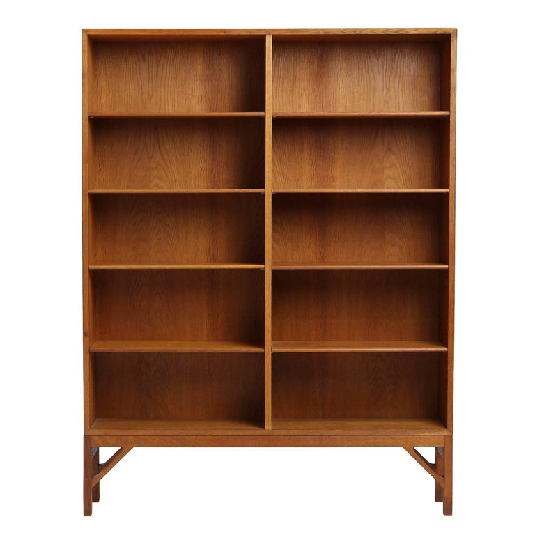 A spare and elegant Scandinavian Modern standing bookshelf / bookcase designed by Borge Mogensen. Unit is constructed in solid active-grained oakwood with adjustable shelves and an architectural base with trussed supports. Made in Denmark, circa