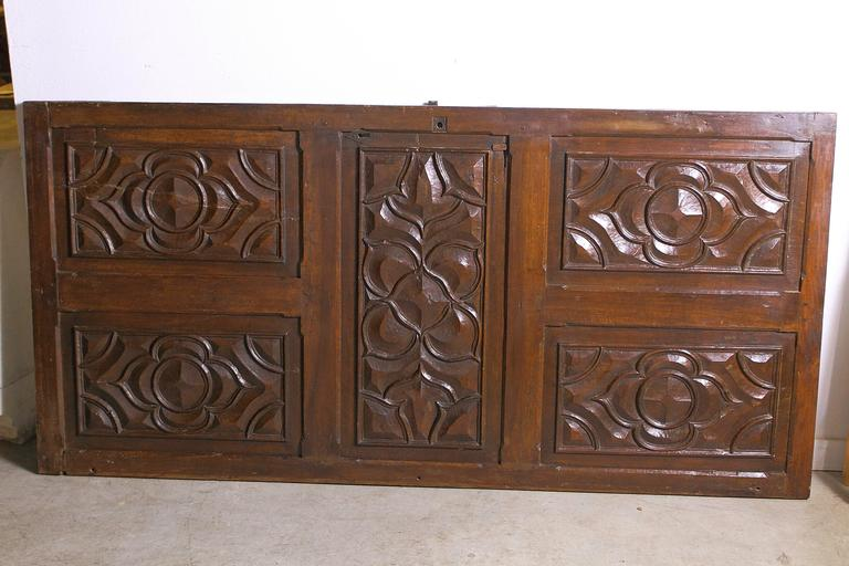 This bold walnut wood door from the 1600's is from the area of Languedoc, in southern France.  The hand carved, raised, beveled motifs are Gothic quatrefoil and cinquefoil cusps.  The carving is deep and shows flawless hand carved shapes. There are