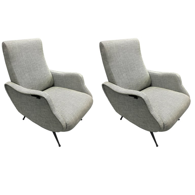 Elegant pair of Italian Mid-Century Modern reclining armchairs in the style of Marco Zanuso's Lady chairs. The pieces have generous size, recline and are very comfortable; they feature exquisite lines and detailing and have black lacquered legs.