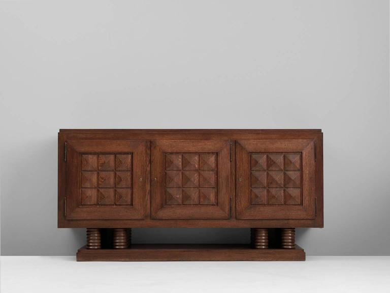 Credenza, in stained oak, by Gaston Poisson, France 1930s.  Sturdy credenza in oak with graphical doorpanels and parquet top. This three-door sideboard is equipped with several shelves and drawers which provide plenty of storage space. The shelves